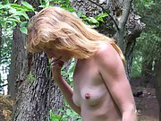 Mature woman poses nude near the lake