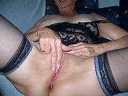 Mature woman masturbates with dildo while dressed in black lingerie