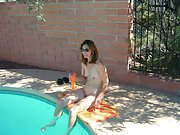 Blonde wife sits naked by the side of the pool