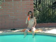 Beautiful woman strips and relaxes naked by the swimming pool