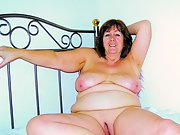 Mature wife shows off her large tits and curves in bed