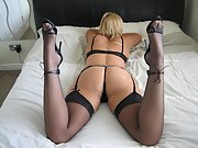 Blonde wife in black stockings and high heels poses on the bed