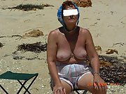Mature blonde wife sits outside naked sun bathing in her yard