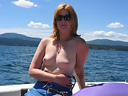 Blonde wife goes topless outside in a boat on the lake