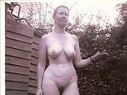 Mature wife poses around the house naked with her big tits