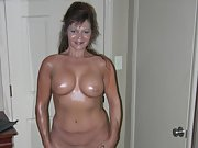 Horny wife shows off her round tits covered in oil