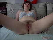 Mature brunette shows her hairy pussy and gives a handjob
