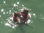 Blonde milf with legs wrapped around her lover in sea caught by voyeur
