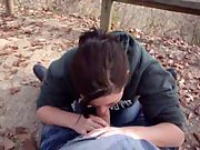 Yougn brunette with massive knockers gives blowjob down by the river